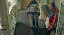 A man dressed as Batman and a burglary suspect stand in a police station in Bradford, northern England, on February 25, 2013, in this still photograph taken from video and provided by West Yorkshire Police on March 4, 2013. (HANDOUT/Reuters)