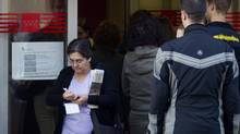 A woman leaves as others queue to enter an unemployed registry office in Madrid. (Paul White/AP)