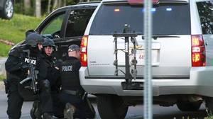 Emergency response team members take cover behind vehicles in Moncton on June 4, 2014.
