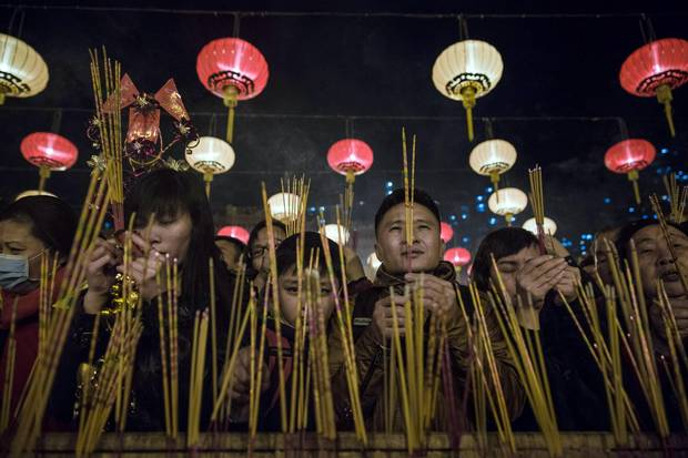 People pray and burn joss sticks at Wong Tai Sin temple to welcome in the Lunar New Year in Hong Kong early on February 8, 2016.