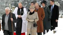 Britain's Queen Elizabeth, centre, and her husband Prince Philip, Duke of Edinburgh, third right, accompanied by an unidentified member of the clergy, arrive with others at the church of St.Peter and St. Paul at West Newton, eastern England, Feb. 5, 2012. (Chris Jackson/AP/Chris Jackson/AP)
