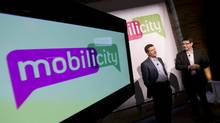 John Bitove, chairman of DAVE wireless, and Dave Dobbin, former president, present their new brand name and logo, Moblicity, on Feb. 2, 2010 in Toronto. (Peter Power/The Globe and Mail)