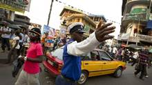 A police officer directs traffic in a bustling downtown intersection in Freetown, Sierra Leone. (Peter Power/The Globe and Mail)