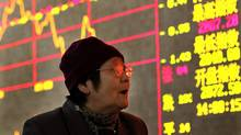 An investor looks at the stock prices monitor at a private securities company in Shanghai. (ASSOCIATED PRESS)
