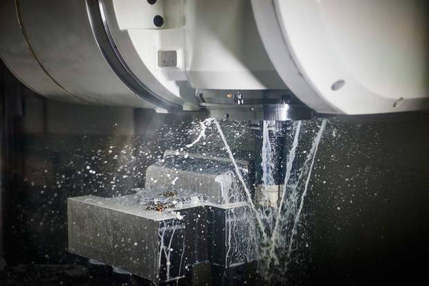 The six-axis drill cuts a part for a V6 engine-block tool. The drill is sluiced with fluid to prevent overheating.