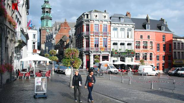 Colourful old buildings and many outdoor cafés surround the Grand Place of Mons in the historic heart of the city.