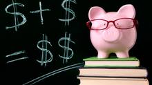 A piggy bank with glasses sits on a pile of books, with dollar signs written on a black board behind it. (David Franklin/Getty Images/iStockphoto)