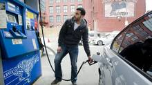 A motorist fills his car with gas in Montreal in this 2012 file photo. (For The Globe and Mail)