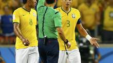 Spanish referee Carlos Velasco Carballo shows Brazil's Thiago Silva the yellow card during Friday's quarter-finals. Velasco Carballo's refereeing resulted in a brutal tempo that favoured Brazil. (MARCELO DEL POZO/REUTERS)