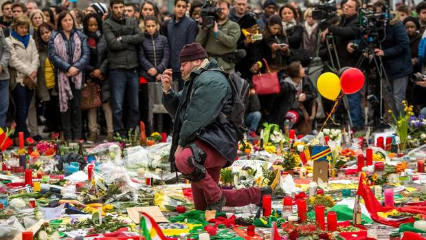 A man kneels and makes the sign of the cross during a minute of silence held at a makeshift memorial in front of Brussel's Stock Exchange in March, 2016. It was two days after a triple bomb attack, claimed by the Islamic State group, which hit Brussels' airport and the central metro station, killing 31 people and wounding 300 others.