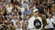 Eugenie Bouchard of Canada holds her runners-up trophy during the trophy ceremony after losing to Petra Kvitova of the Czech Republic in the women's singles final match at the All England Lawn Tennis Championships in Wimbledon, London, Saturday, July 5, 2014. (Sang Tan/AP)