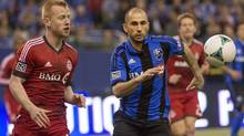Toronto FC Richard Eckersley left, races Montreal Impact Marco Di Vaio right for the ball during first half MLS action at the Olympic Stadium in Montreal on Saturday March 16, 2013. (Peter McCabe/THE CANADIAN PRESS)