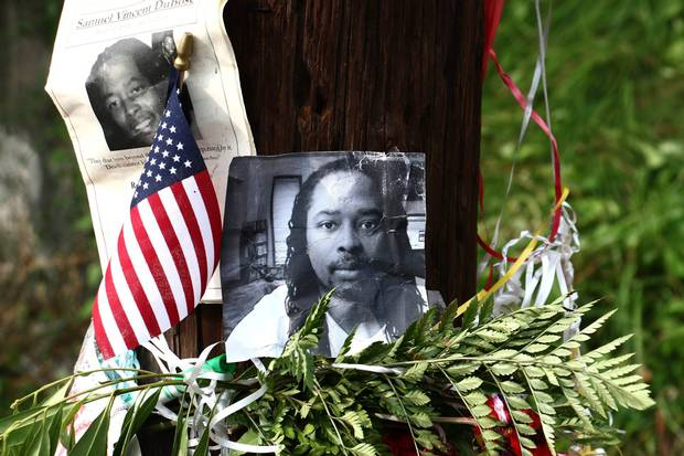 Photos of Samuel DuBose hang on a pole on July 29, 2015, at a memorial near where he was shot and killed.