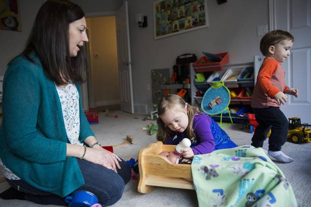 Mary Casagrande plays with her daughter Emma, 4, who has Down syndrome, while also watching one of her two sons Tommy, 20 months, in Guelph, Ont., on Dec. 1, 2017.