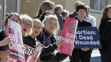 Demonstrators hold up pro-choice signs, left, as an opposing group holds up anti-abortion signs, during a rally to protest South Dakota's new anti-abortion law outside the Federal Court building in downtown Sioux Falls, S.D., March 9, 2006. (NATI HARNIK/AP/NATI HARNIK/AP)