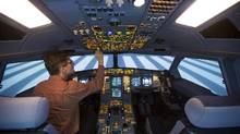 A technician operates a CAE Inc. A330-200 passenger plane flight simulator at the LFT training centre in Berlin. (Handout)