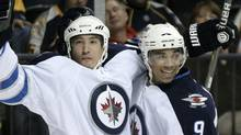 Winnipeg Jets right wing Spencer Machacek, left, celebrates with Evander Kane (9) after scoring against the Nashville Predators in the first period of a preseason NH