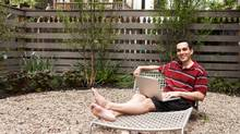 Relaxing on lounge chairs in urban backyard (Chris Clinton/Getty Images)