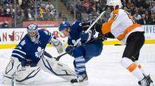 Toronto Maple Leafs goalie James Reimer, left, makes a save as Maple Leafs forward Mikhail Grabovski, centre, battles for the loose puck with Philadelphia Flyers forward Wayne Simmonds, right, during first period NHL action in Toronto on Thursday, April 4, 2013. (Nathan Denette/THE CANADIAN PRESS)