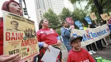 Members of the Ramirez family from Oakland (L-R) Emily, 15, Margarita and Marcus, 4, hold signs outside the Bank of America uptown headquarters before the Bank of America annual shareholder meeting in Charlotte, North Carolina May 9, 2012. (JASON MICZEK/REUTERS)