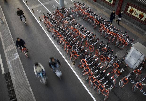 BEIJING, CHINA - APRIL 11: Chinese commuters ride past a large group of Mobike ride share bicycles at a distribution area during rush hour on April 11, 2017 in Beijing, China. The popularity of bike shares has exploded in the past year with more than two dozen providers now battling for market share in major cities across China. The bikes are hailed as an efficient, cheap, and environmentally-friendly solution for commuters, where riders unlock the stationless bicycles using a mobile phone app, drop them anywhere for the next user, and spend as little as 1 yuan ($0.15) per hour. Given the bikes have several users a day - some of them inexperienced riders who swerve into traffic - they are often damaged, vandalized, or abandoned. Companies like Ofo routinely collect the battered two-wheelers and bring them to a makeshift depot that is part repair shop, part graveyard where they are either salvaged or scrapped. The bike shares are powering a cycling revival of sorts in a country once known as the 'Kingdom of Bicycles'. In the early years of Communist China, most Chinese aspired to own a bicycle as a marker of achievement. When the country's economic transformation made cars a more valued status symbol, the bicycle - a Chinese cultural icon - was mocked as a sign of backwardness. The bike share craze is also a boon for manufacturers who are now mass producing over a million bikes a month to meet demand, and the number of shared bike users will reach 50 million in China by the end of the year, according to Beijing-based BigData Research. Not everyone is cheering the revival though, as municipal officials are drafting new regulations to control the chaotic flood of bicycles on streets and sidewalks. (Photo by Kevin Frayer/Getty Images)