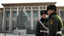 In this Wednesday, Jan. 12, 2011 photo, Chinese paramilitary policemen stands guard in front of a sculpture of the ancient philosopher Confucius on displayed in near the Tiananmen Square in Beijing, China's capital. The mammoth sculpture of Confucius was unveiled this week off one side of the giant plaza, the political heart of China. It's a curious juxtaposition for a site that's heavy with Communist history _ Mao's body is interred in the middle of it and his giant portrait hangs at one end. (Andy Wong/The Associated Press/Andy Wong/The Associated Press)