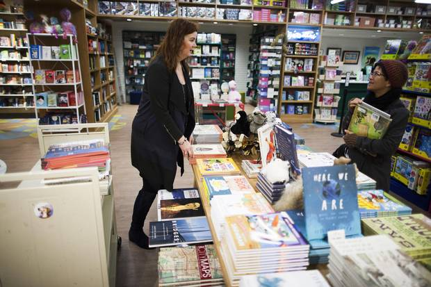 Kelly McKinnon, left, co-owner of KidsBooks, helps a customer.