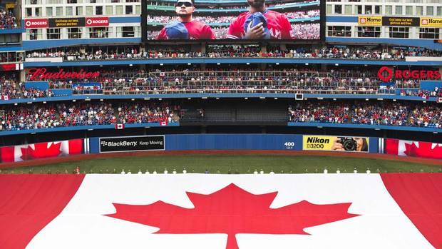 A giant Canadian flag is seen during the national anthem to commemorate Canada Day before the Toronto Blue Jays play Detroit Tigers in their MLB American League baseball game in Toronto, July 1, 2013. (MARK BLINCH/REUTERS)