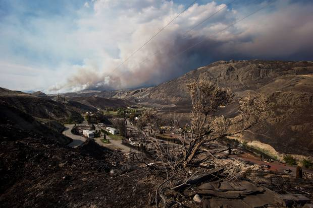 July 9, 2017: A burnt tree is seen in the foreground above the remains of mobile homes destroyed by wildfire in Boston Flats, near Ashcroft, B.C.