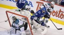 Vancouver's Henrik Sedin, left, and San Jose's Justin Braun are pushed into Sharks goaltender Antti Niemi's net by Marc-Edouard Vlasic of the Sharks while Alex Burrows of the Canucks controls the puck during the second period of Game 1 in Vancouver on Wednesday night. (John Lehmann/The Globe and Mail)