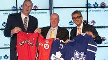 George Cope, president and CEO of Bell Canada, left,  MLSE Chairman Larry Tanenbaum, centre, and Nadir Mohamed President and CEO of Rogers Communications hold up Toronto Raptors, Toronto FC, Toronto Maple Leafs and Toronto Marlies jerseys following a press conference in Toronto on Friday December 9, 2011. (The Canadian Press)
