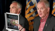 Douglas Keefe, left, and John Furlong display their report on the Stanley Cup riot at a news conference in Vancouver on Sept. 1, 2011. (Jeff Vinnick For The Globe and Mail/Jeff Vinnick For The Globe and Mail)