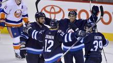 Winnipeg Jets' Olli Jokinen (12) celebrates with, from left, Dustin Byfuglien, Tobias Enstrom and Evander Kane after defeating the New York Islanders in overtime during their NHL hockey game in Winnipeg January 27, 2013. (FRED GREENSLADE/REUTERS)