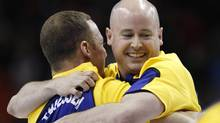 Alberta skip Kevin Koe, right, celebrates with lead Nolan Thiessen after they defeated Ontario to win the Tim Hortons Brier curling championships in Halifax. (SHAUN BEST/Shaun Best/Reuters)