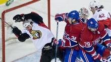 Ottawa Senators' Zenon Konopka, left, collides with Montreal Canadiens' Alexei Emelin (74) as Canadiens' goaltender Carey Price, centre, Andrei Markov (79) and Senators' Jim O'Brien look for the puck during second period NHL hockey action in Montreal, Friday, March 23, 2012. THE CANADIAN PRESS/Graham Hughes (Graham Hughes/CP)