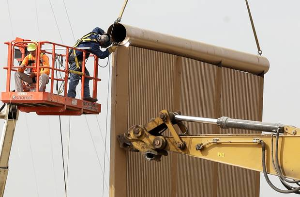 Crews work on a wall prototype near the border with Tijuana, Mexico, Thursday, Oct. 19, 2017, in San Diego.