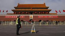 A policeman blocks the street in front of the giant portrait of former Chinese chairman Mao Zedong at Beijing's Tiananmen Gate Nov. 7, 2012. (PETAR KUJUNDZIC/REUTERS)
