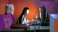 A women at an internet cafe in Beijing, July 28, 2011. (SIM CHI YIN/For The Globe and Mail)