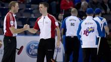Newfoundland and Labrador skip Brad Gushue, centre, celebrates his teams with over British Columbia with lead, Geoff Walker following the afternoon draw at the Tim Hortons Brier in Edmonton, Alta. Tuesday, March 5, 2013. (JONATHAN HAYWARD/THE CANADIAN PRESS)