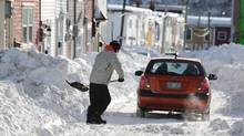 A man shovels the snowy street of St. John's on Jan. 5, 2014. (PAUL DALY/THE CANADIAN PRESS)