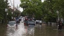 Cars are towed on a flooded street in Montreal, May 29, 2012. Flash flooding occurred after heavy thunderstorms blew across the island. (Christinne Muschi/Reuters/Christinne Muschi/Reuters)