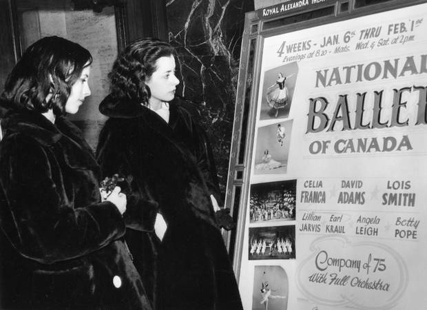 NATIONAL BALLET OF CANADA -- Georgina Parkinson and Hylde Zinkin look over National Ballet of Canada lobby poster advertising performances at the Royal Alexandra Theatre in Toronto, January 1958.