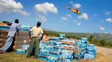 At Jacmel, Haiti, deliveries come in primarily by helicopter, small planes, and the occassional hercules c-130 aircraft. Bottled water sits near the tarmac at the airport waiting to be loaded onto trucks and taken to a warehouse. A Canadian helicopter flies overhead. (Peter Power/Peter Power/THE GLOBE AND MAIL)