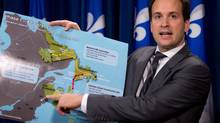 Alexandre Cloutier, junior minister for Canadian Intergovernmental Affairs, holds the Muskrat Falls/Churchill Falls project map as he criticizes the involvement of the federal government in a provincial jurisdiction, Nov. 30, 2012 at the legislature in Quebec City. (Jacques Boissinot/THE CANADIAN PRESS)