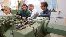 Doug Riffelo, Terry Bigsby and Michael Dan fine-tune a veneer lathe for Aspenware, a business on the Wabauskang First Nations Reserve. (Bernie Farber)