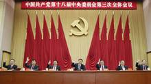 In this photo released by China's Xinhua news agency, Chinese President Xi Jinping, center, and other Communist Party top leaders raise their hands to vote in the third plenary session of the 18th Central Committee of the Communist Party of China, in Beijing on Nov. 12, 2013. (Lan Hongguang/Associated Press)