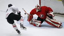 Goalie Jordan Binnington (R) stops a shot by Hunter Shinkaruk in the first period during the red-white team game at the Team Canada selection camp in Calgary, Alberta, December 11, 2012. (TODD KOROL/REUTERS)