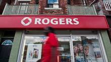 A man walks by a Rogers store in Toronto in this file photo. (Galit Rodan/The Canadian Press)