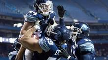 Toronto Argonauts linebacker Jason Pottinger, top left, reacts after scoring a touchdown past the Edmonton Eskimos during first half CFL Eastern Conference semi final action in Toronto on Sunday, Nov. 11, 2012. (Nathan Denette/THE CANADIAN PRESS)