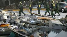Soldiers patrol next to debris caused by a blast at the Pemex complex in Mexico City on Friday. (MARCO UGARTE/ASSOCIATED PRESS)